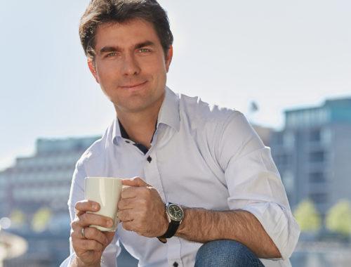 Mark Helfrich hält Kaffeetasse in der Hand
